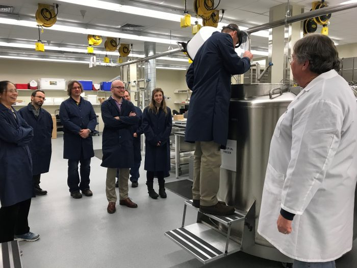Staff in blue coats touring a lab.