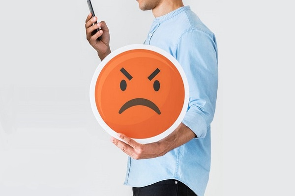 man holding phone and angry face emoji icon
