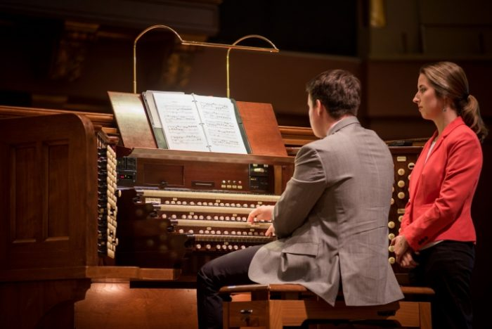 Young man sitting at organ, woman standing next to him.