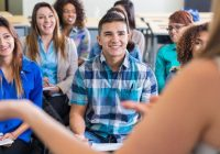 Teens smiling while listening to speaker during presentation in school