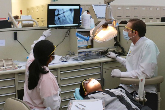 Dentist and hygienist look at monitor, patient in chair.