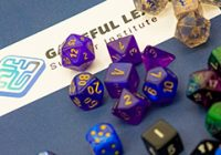 multicolored gaming dice on table next to Gameful Leaning card
