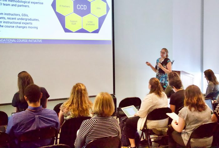 Woman giving presentation to room of people