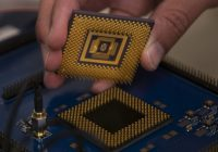 hand holding memristor over circuit board
