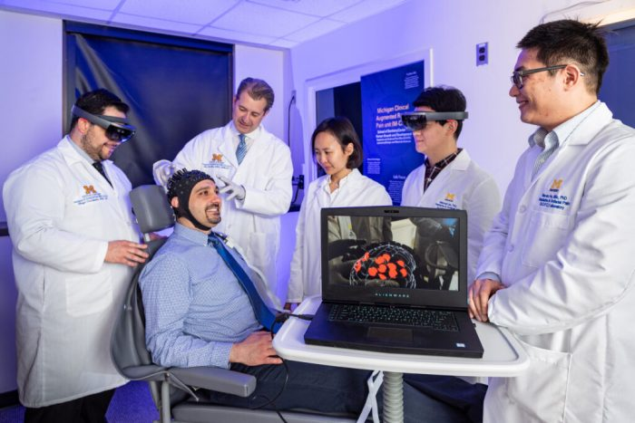 Man wearing neuro cap surrounded by clinicians, laptop with brain scan on monitor.