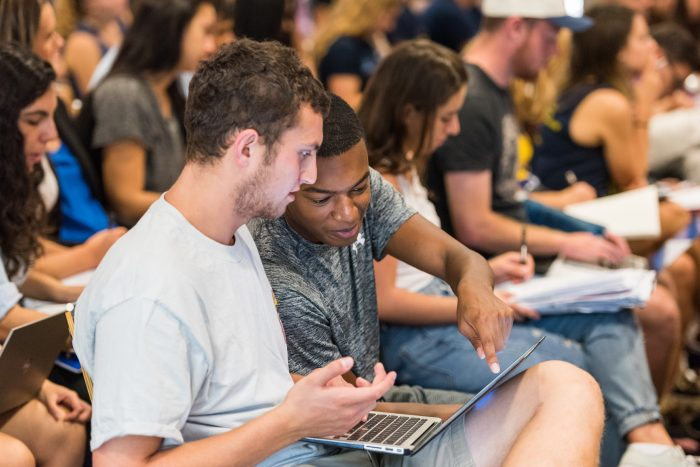 Two men discuss something over a laptop in a lecture hall.