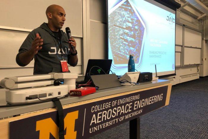 African-American man wearing JAIC sweatshirt giving a presentation.