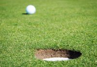 golf ball next to hole on putting green