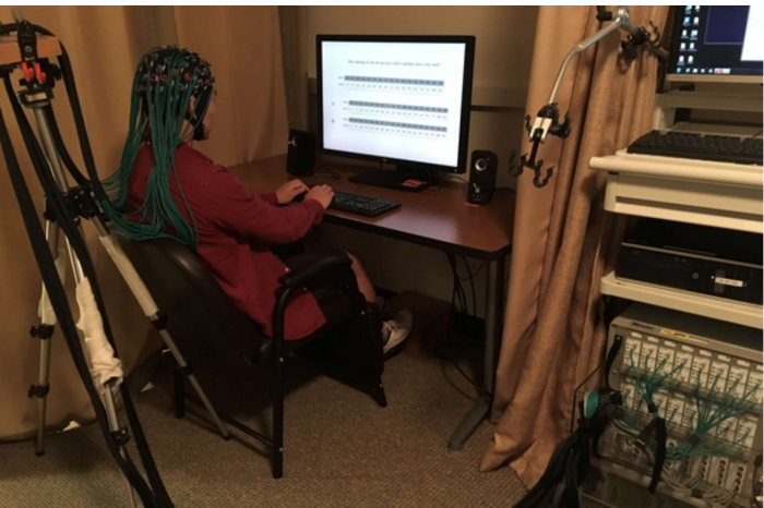 programmer at computer with headset connected to neural transmitters