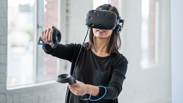 Woman wearing VR/AR goggles, holding controllers.
