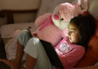 Girl sits on sofa using tablet, a pink teddy bear next to her