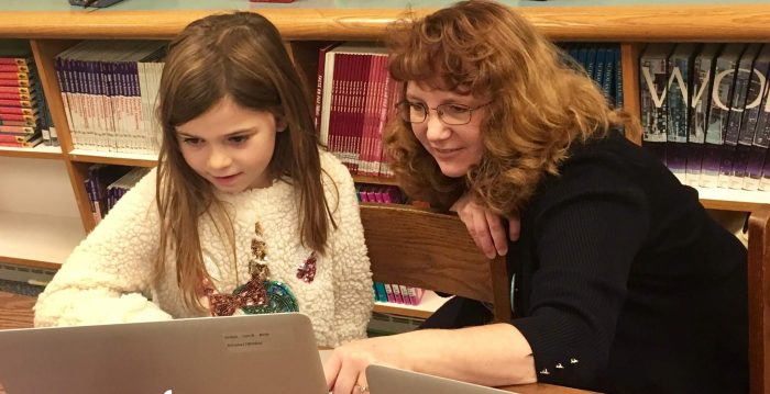 A young girl and a women look at a laptop together. They are sitting in front of a bookcase.