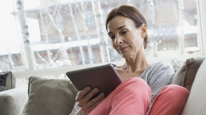 woman on sofa looking at tablet device