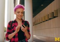 young woman with pink hair using her phone
