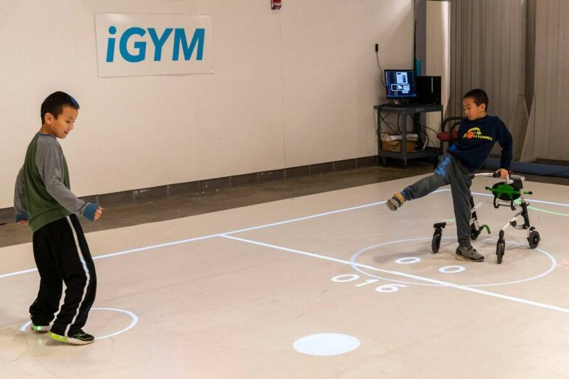 two boys, one in a wheelchair, playing iGym game.