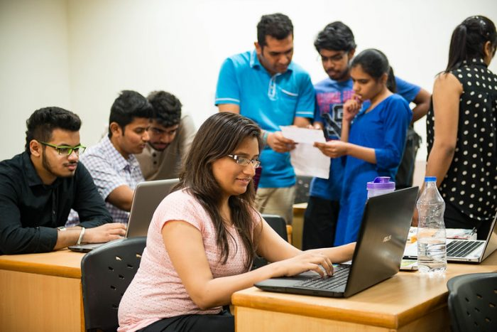 Group of Indian students sitting at tables and working on computers.