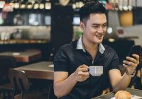 asian man drinking coffee looking at phone