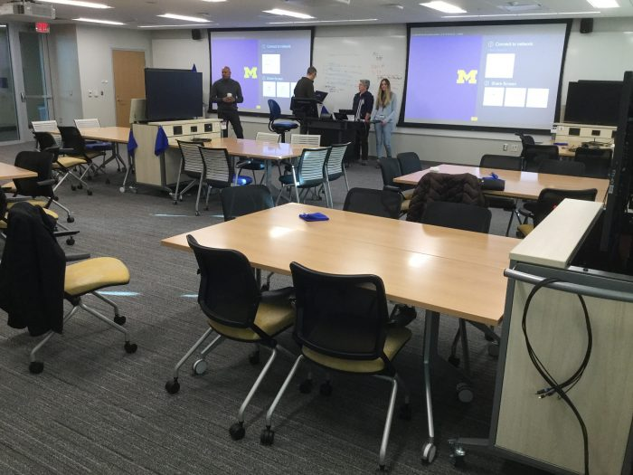 A view from the back of the team-based-learning classroom at 1280 LSA, with two large projection screens and four individuals at the front of the room.