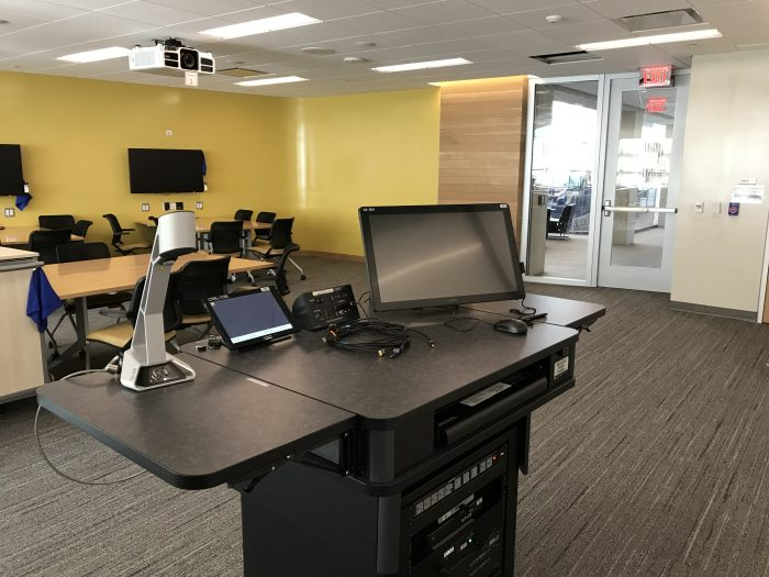 LSA classroom podium: Document camera on left, control pad on the middle-left, cable connections on the middle-right, and touch-screen monitor on the right.