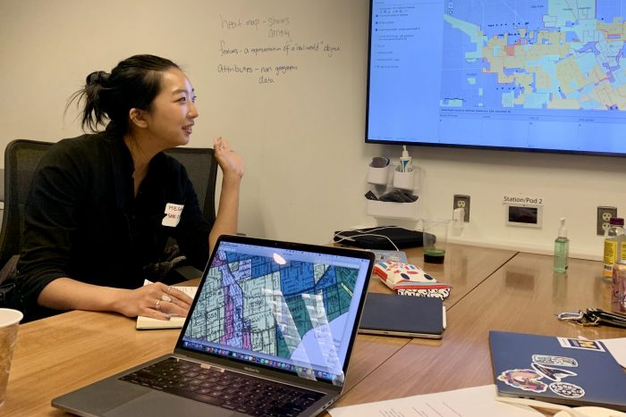 Asian woman sitting at table looking at map on wall screen.