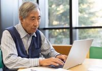 senior Asian man sitting at table working on computer
