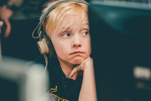 boy wearing headphones, sitting behind computer