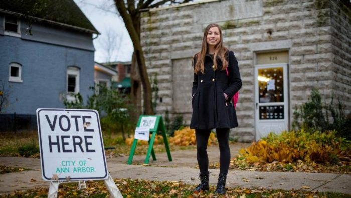 """young blond woman wearing a blue coat stands in front of a building next to a """"Vote Here"""" sign."""