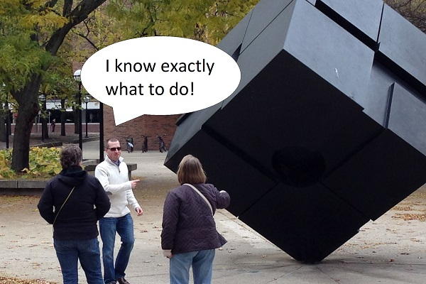 Three people standing near the cube. Word bubble: I know exactly what to do!