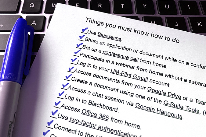 checklist and blue marker on laptop keyboard