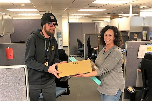 Male ITS worker handing box of equipment to female staffer.