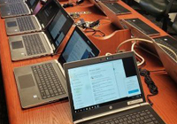 Table with dozens of laptops,