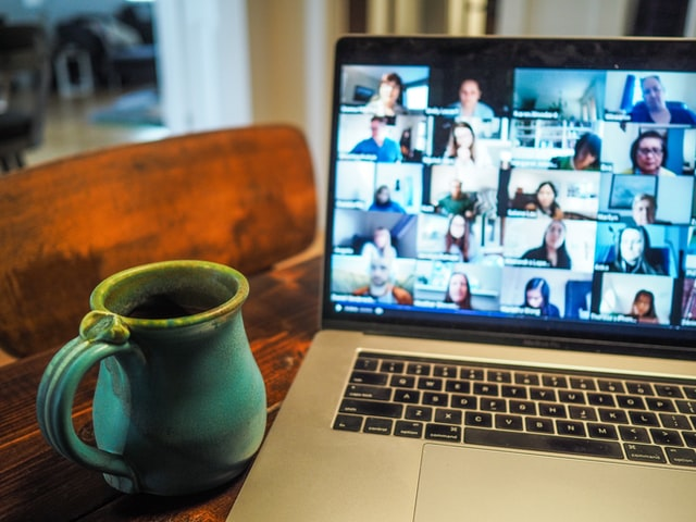 laptop on table with large video conference on screen, coffee mug to the left