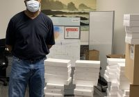 A School of Dentistry staffer stands next to piles of iPads.