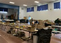 (A small gymnasium filled with opened and unopened cardboard boxes sitting on tables.)