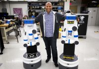 (Chad Jenkins standing with his arms around two robots that almost reach his shoulders standing upright.)