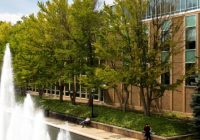 (Photo of a building with trees and a fountain in front of it.)