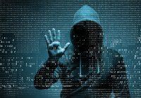 hooded hacker behind wall of digital numbers