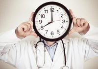 Man in lab coat with stethoscope holds clock in front of his face.