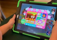 (iPad screen showing a child's game with a cartoon dog working a food stand and a monkey sitting at a desk with books. The iPad is held by a child's hands.)