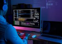(Image of a computer monitor showing code in a dark, glowing pinkish purple room with a man typing on the keyboard.)
