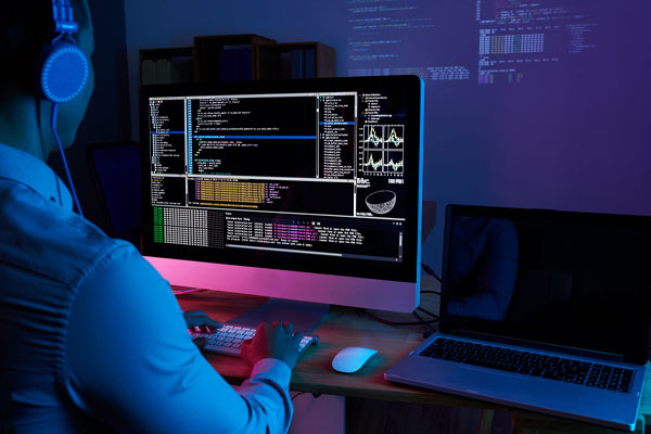 (Computer monitor showing code in a dark, glowing pinkish purple room with a man typing on the keyboard.)