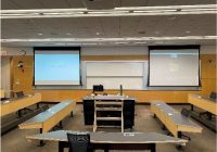 A classroom at the Ross School of Business that includes an instructor's desk in the middle, rows of desk on either side of instructor's desk, and two screens that display classroom content.