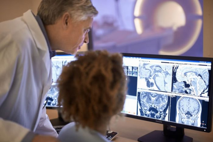 Man and woman in lab coats viewing MRI images on computer monitor