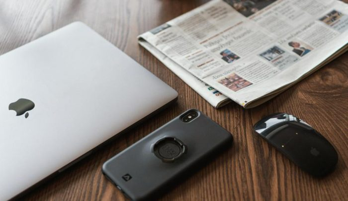 black smartphone on table next to laptop and newspaper