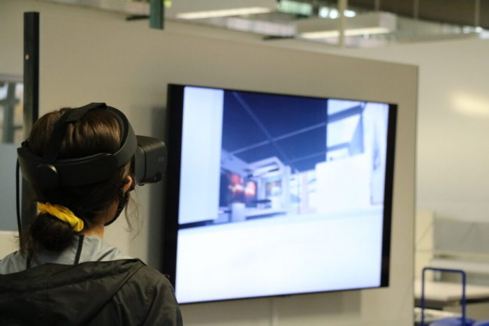 Female student wearing VR headset, large monitor in the background.