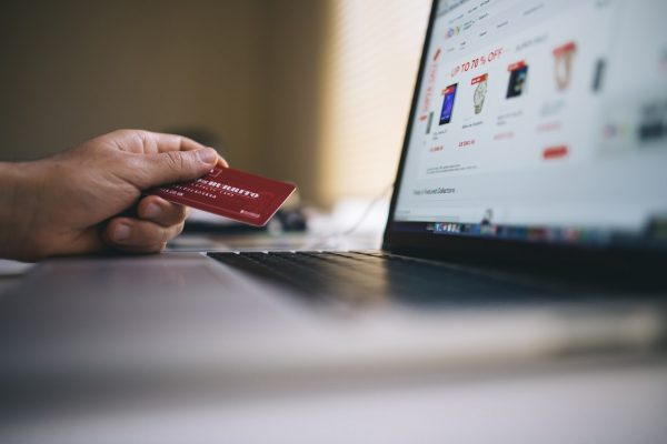 hand holding credit card, hovering over laptop keyboard, shopping sites on the monitor