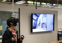 female student wearing VR headset using hand conrollers, monitor in background