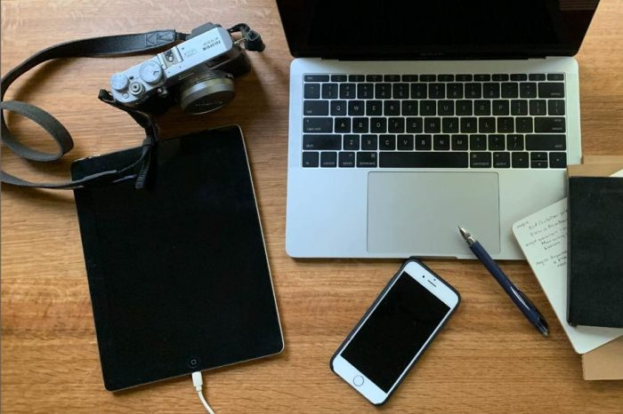 laptop, camera, tablet, iphone, pen and notepads arranged on tabletop