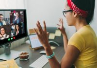 Young woman sitting at computer, videoconferencing with colleagues