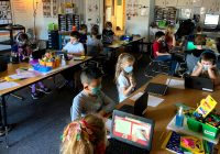 Classroom of masked children working on laptops.